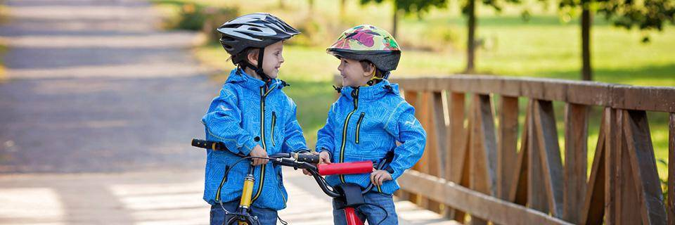 Two little brothers laughing on bikes