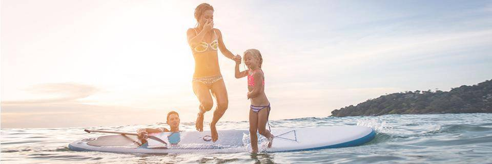A family jumping off a SUP into the sea