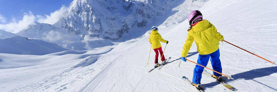 Two people skiing down the mountain