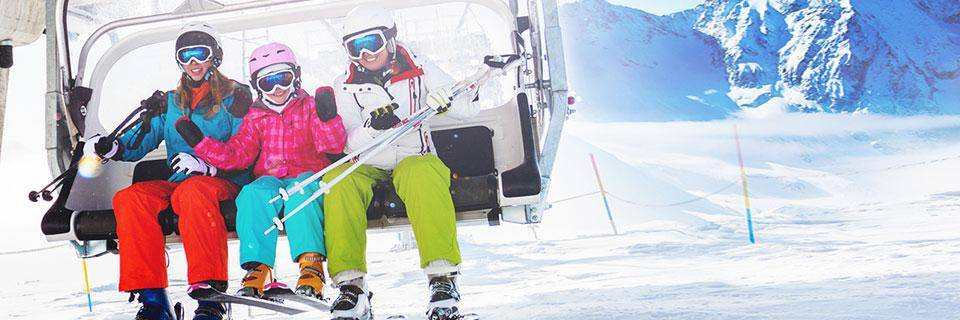 Family sitting on a ski chair lift