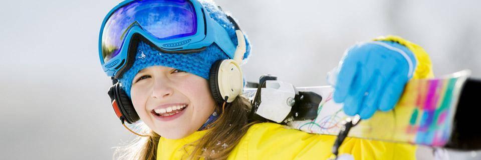 Little girl holding her skis over her shoulder