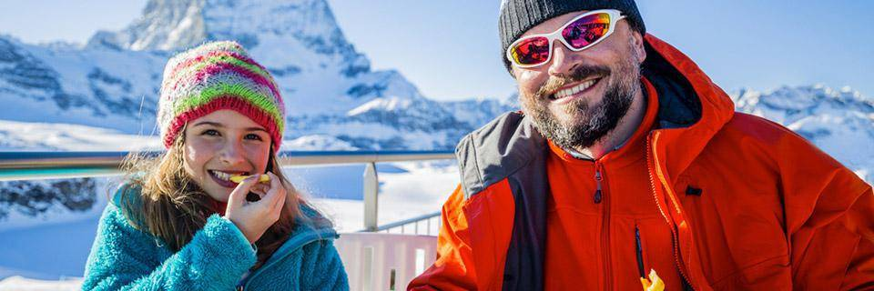 Father and daughter eating on a French Alps ski holiday